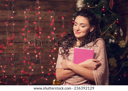 Cute woman with candle next to christmas tree