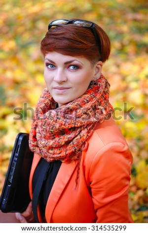 Cute woman with laptop in the autumn park