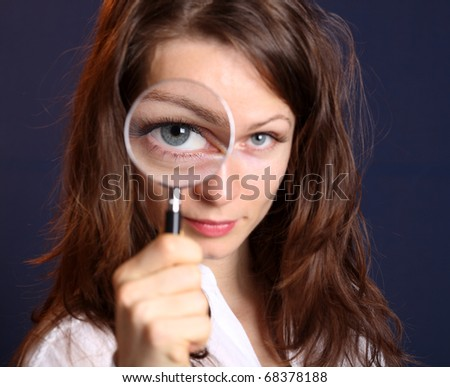Cute woman with magnifying glass - stock photo