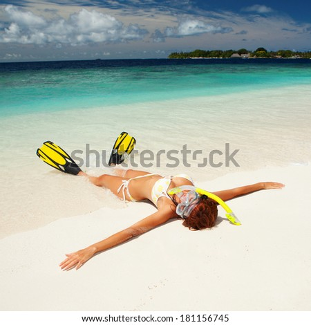 Cute woman with snorkeling equipment relaxing on the tropical beach - stock photo
