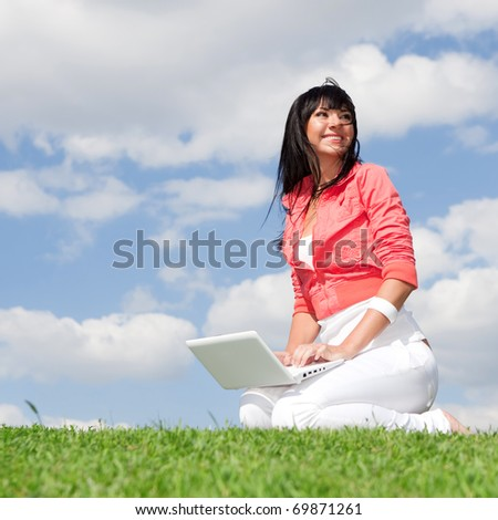 Cute woman with white laptop in the park - stock photo