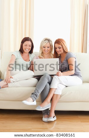 Cute women relaxing on a sofa with a laptop in a living room
