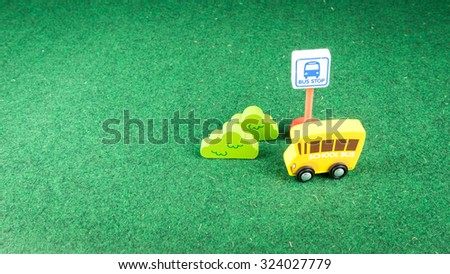 Cute wooden bushes, bus stop sign and single decker school bus on green grass background. Concept of safety education and back to school. Slightly de-focused and close-up shot. Copy space. - stock photo