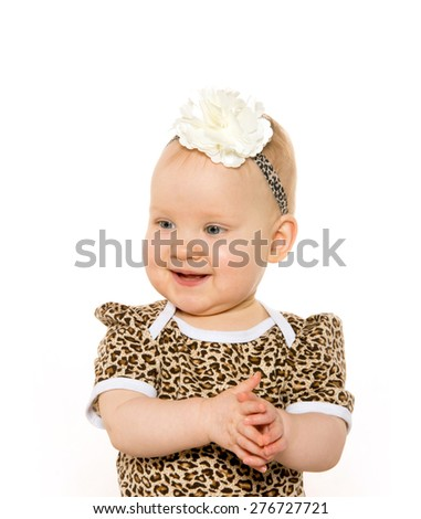 Cute 1-year-old baby girl with blond hair and blue eyes and a leopard print shirt isolated on white background - stock photo