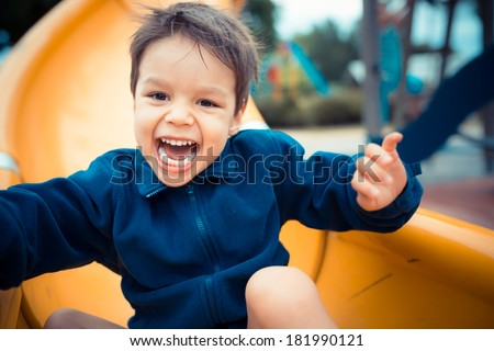 Cute 3 year old boy excitedly plays on a yellow playground slide on a cool cloudy day - stock photo