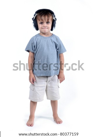 Cute 3 - 4 year old boy standing with headset isolated on white