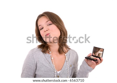 Cute 13 year old checking her makeup in a hand mirror