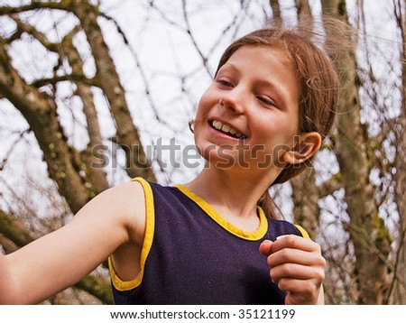 Cute 8 year old girl is playing and looking at something to the side. - stock photo