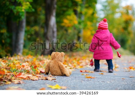 Cute 1 year old girl walking outdoors at autumn day. Focus on teddy bear - stock photo