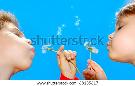 cute 4 year old girls blowing dandelion seeds away - stock photo