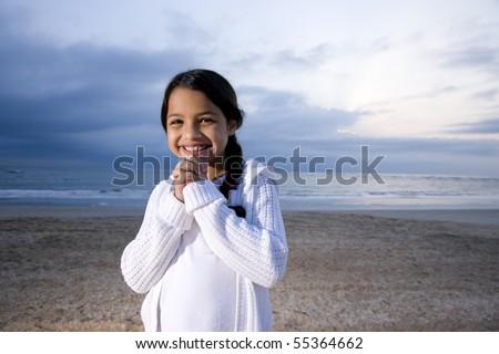 Cute 9 year old Hispanic girl smiling on beach at dawn - stock photo