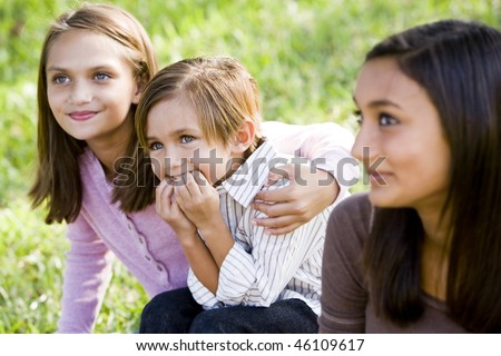 Cute 5 year old little boy with affectionate older sisters together on grass outdoors - stock photo
