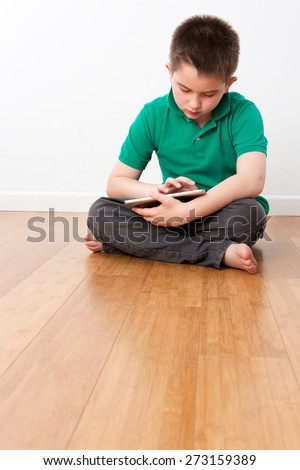 Cute 10 Year Old Male Kid Sitting on the Floor with Legs Crossed, Playing at his Portable Tablet Computer Seriously. - stock photo