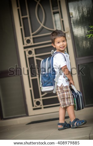 Cute 3 year old mixed race Asian Caucasian boy confidently leaves home for his first day at preschool - stock photo