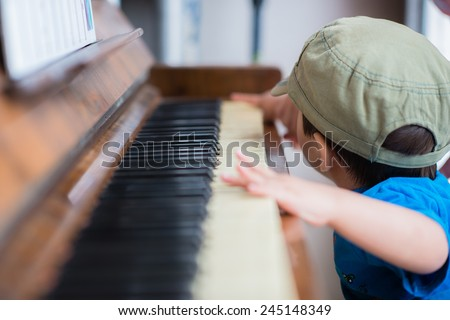 Cute 2 year old mixed race Asian Caucasian boy plays an old piano like a pro musician - stock photo