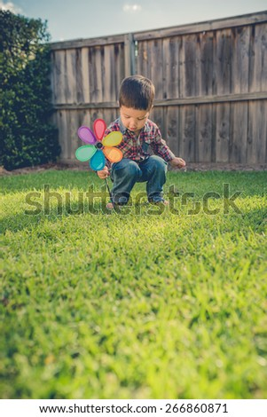 Cute 2 year old mixed race Asian Caucasian boy plays with a garden ornament in the backyard of his suburban home. Filtered effects - stock photo