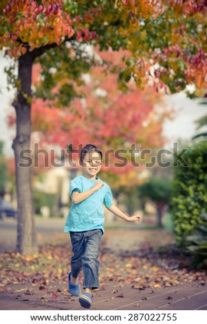 Cute 5 year old mixed race Asian Caucasian boy runs down the footpath (sidewalk) of his suburban neighborhood with beautiful Autumn (Fall) trees lining the street - stock photo