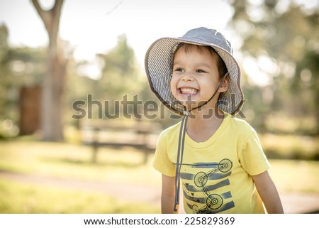 Cute 4 year old mixed race Asian Caucasian boy wearing a hat and playing outside in the summer sun - stock photo
