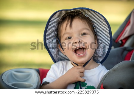 Cute 2 year old mixed race Asian Caucasian boy wearing a hat and playing outside in the summer sun - stock photo