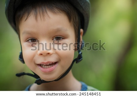 Cute 4 year old mixed race Asian Caucasian boy wears a bike helmet outside with a soft natural green background and copy space - stock photo