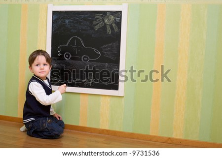 Cute 3 years old boy draws a car on blackboard - stock photo