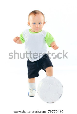 Cute 1 years old boy in sports form with a soccer ball in the studio