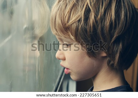 Cute 6 years old boy looking through the window - stock photo