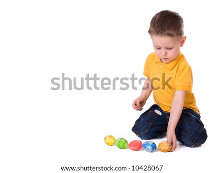 Cute 3-years old boy playing with Easter eggs. Isolated on white. - stock photo