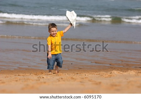 Cute 3-years old boy running with plane made from newspaper
