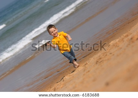 Cute 3-years old boy running with plane made from newspaper - stock photo