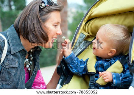 Cute 2 years old boy shows his mother a flower in the park - stock photo