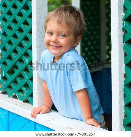 Cute 2 years old boy sitting in the summer house in park - stock photo
