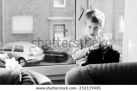 Cute 6 years old boy sitting near the window - stock photo