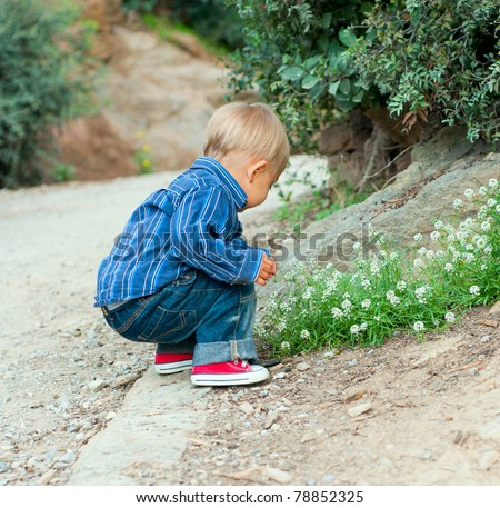 Cute 2 years old boy sitting on the footpath in the park - stock photo
