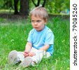 Cute 2 years old boy sitting on the grass in the park - stock photo