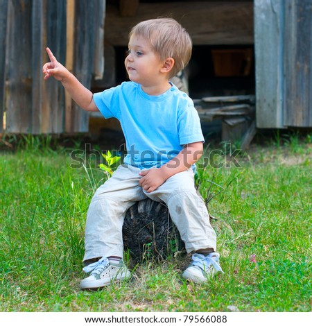 Cute 2 years old boy sitting on the the bench in the park - stock photo