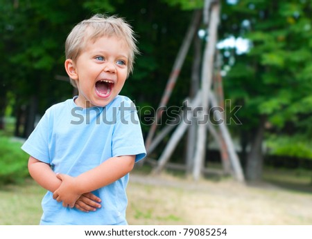 Cute 2 years old boy staing on the footpath in the park - stock photo