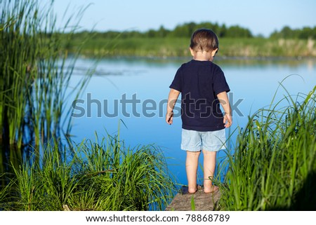 Cute 2 years old boy stands and looking at the river - stock photo