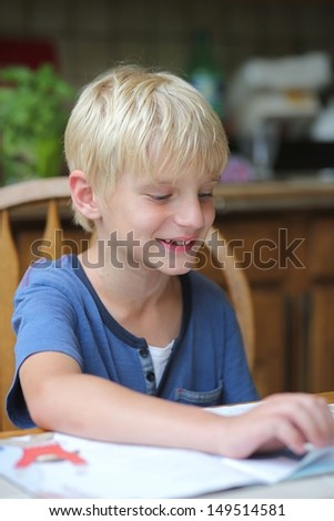 Cute 7 years old boy studying after school, sitting on a chair in the kitchen, reading his book and smiling - stock photo