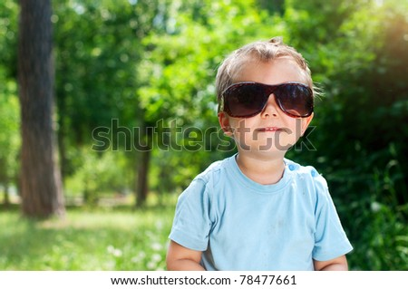 Cute 2 years old boy Sunglasses outdoors at sunny summer day - stock photo