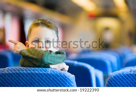 Cute 4-years old boy traveling by train - stock photo