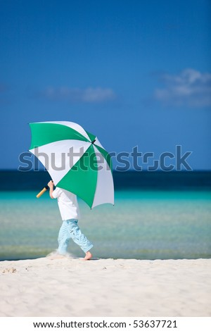 Cute 5 years old boy with big umbrella on tropical beach - stock photo