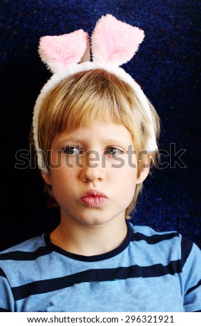 Cute 7 years old boy with bunny ears - stock photo
