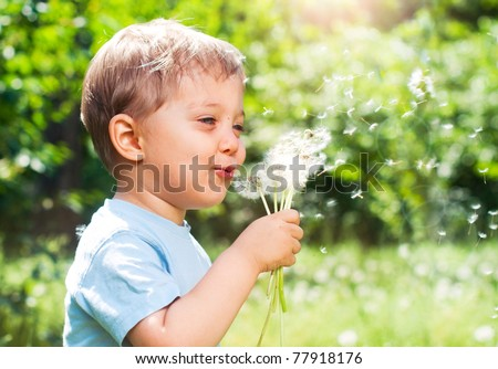 Cute 2 years old boy with dandelion outdoors at sunny summer day - stock photo