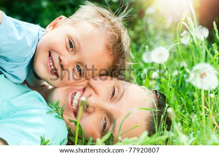 Cute 2 years old boy with mother lying in the grass at sunny summer day - stock photo