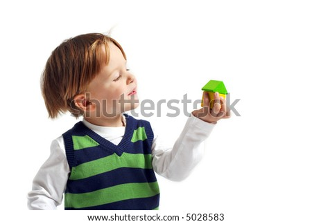 Cute 3-years old boy with small house built from wooden blocks. Isolated on white background.