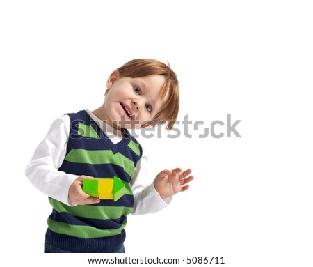 Cute 3-years old boy with small house built from wooden blocks. Isolated on white background. - stock photo