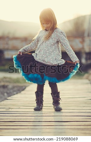 Cute 5 years old girl wearing tutu skirt posing over sunset sunlight in rustic scene - stock photo