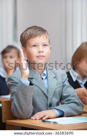Cute 8-9 years schoolboy. Real lesson in classroom. - stock photo