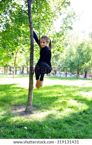 Cute young acrobat having fun outdoor training uses a tree as a gymnastic pole.  - stock photo